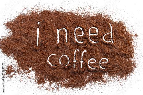 Fotografia, Obraz ground coffee sprinkled on a white table, text I need coffee