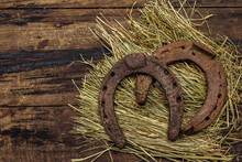 Two Very Old Cast Iron Metal Horse Horseshoes On Hay. Good Luck Symbol, St.Patrick's Day Concept. Antique Wooden Background