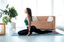 Beautiful Latin Woman Doing Yoga At Home. Pigeon Pose