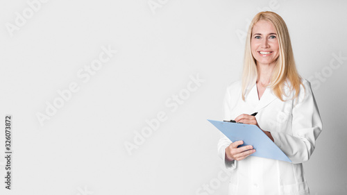 Photographie Middle aged woman holding clipboard writing diagnosis
