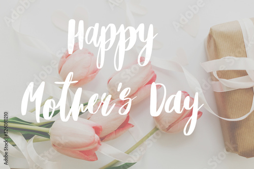 Happy mother's day.  Happy mother's day text and pink tulips with gift box on white background. Stylish soft image. Floral Greeting card. Happy Mothers day. Handwritten lettering
