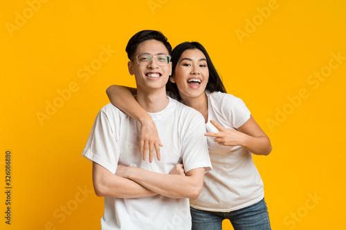 Portrait of joyful asian couple posing over yellow background Poster Mural XXL