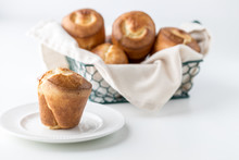 Close Up Of A Basket Filled With Popovers With A Popover On A Plate In Front.