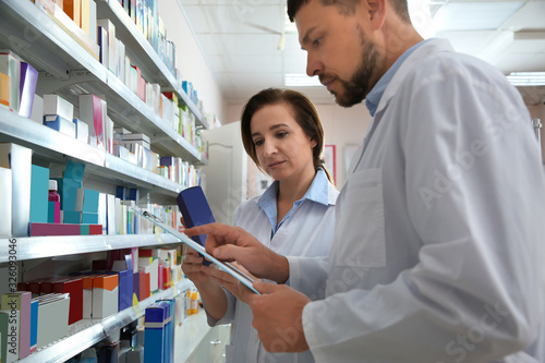 Photo Professional pharmacists near shelves with medicines in modern drugstore