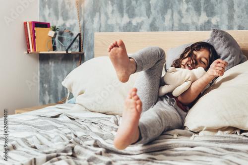 Fototapeta little girl jumping at bed falls on the cushions obraz na płótnie