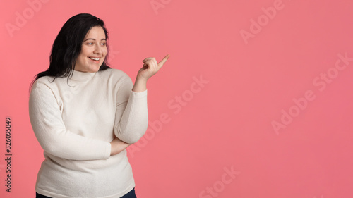 Cheerful Obese Girl Showing Aside With Finger Over Pink Background Canvas Print