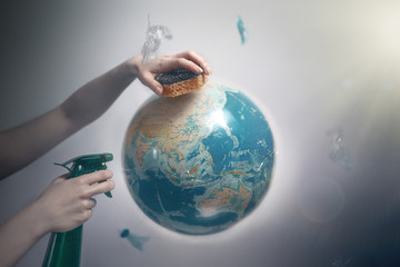 Woman's hand holding a sponge and spray to clear the planet Earth. The concept of improving the state of the environment, Earth Day. Tint