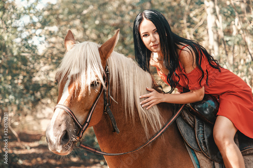 A brunette woman in a red dress sits astride a brown horse and smiles sweetly Canvas Print