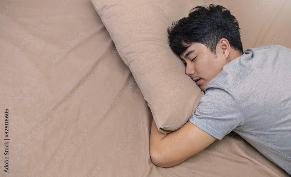 Fototapeta Portrait of young asian man with attractive smile sleeping laying indoor apartment bed room . Asian man sleep tight in bed with copy space. Healthy care good night sleep concept