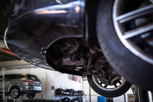 Photo Car in a garage for maintenance, oil/tyre change (shallow DOF; color toned image