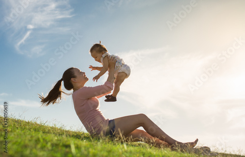 A mom adoring her child sitting on the grass, enjoying a fun summer day together Canvas Print