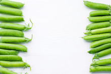 Fresh Green Pea Pods On A White Painted Surface, Top View, Copy Space