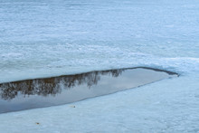 An Ice Hole In A Frozen Pond B...