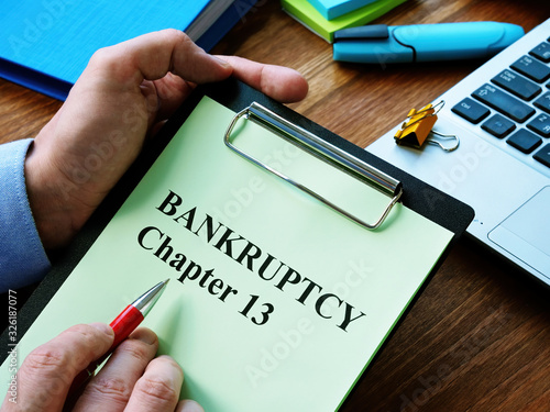 Photo Man reads bankruptcy chapter 13 law in the office.