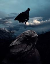Levitating Hooded Figure Over Rock And Dark Landscape