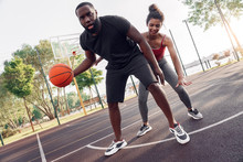 Outdoors Activity. African Couple Guy Dribbling Breathing Hard While Girl Defencing Backdoor Joyful On Basketball Court