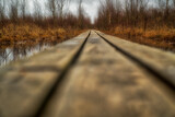 Fototapeta Las - Rickety wooden boardwalk over swamp during rain
