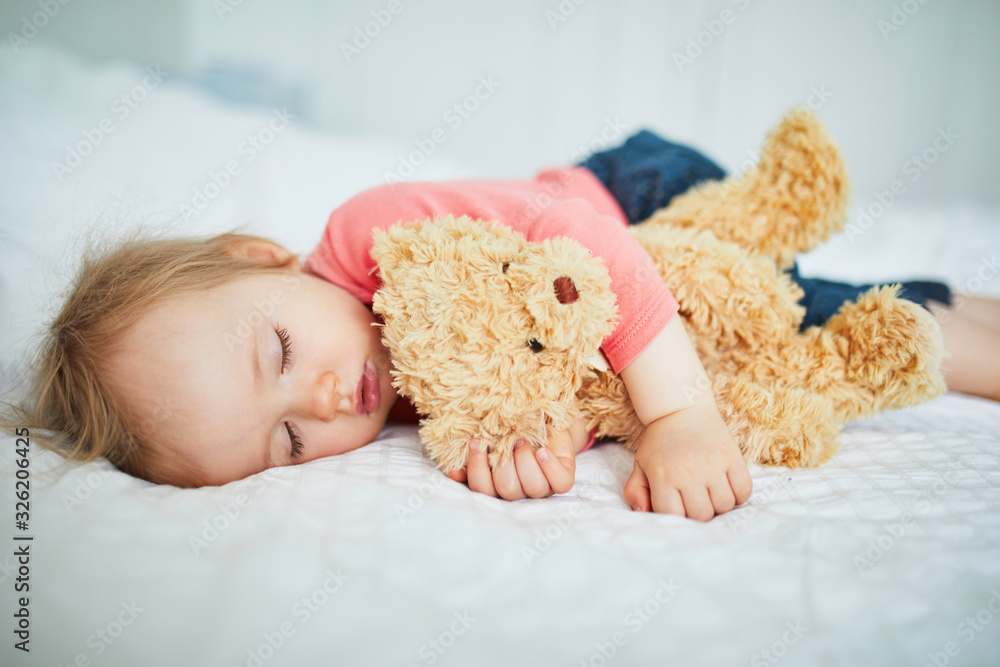 Fototapeta Adorable baby girl sleeping with her favorite toy