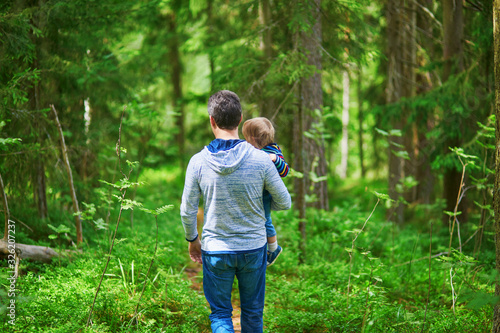 Obraz Father carrying his child during walk in forest - fototapety do salonu