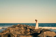 Girl Standing On Rocks Heading...