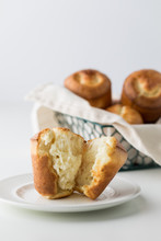 A Close Up Of A Baked Popover On A Plate With A Basket Of Popovers In Behind.