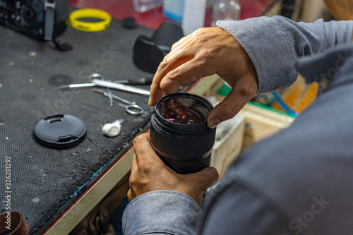 Closeup photo of technician with amputated finger cleaning camera lens Canvas Print