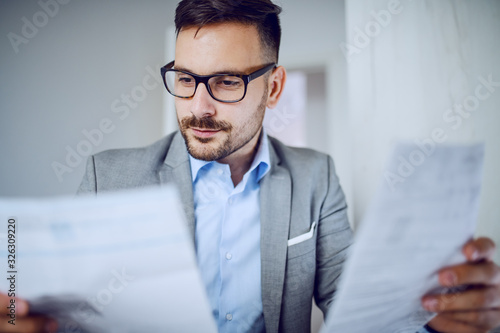 Fotografía Head shot of hardworking sophisticated caucasian businessman in suit and with eyeglasses looking at documents while sitting in his office