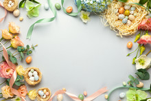 Happy Easter Concept With Easter Eggs In Nest And Spring Flowers. Easter Background With Copy Space. Flat Lay