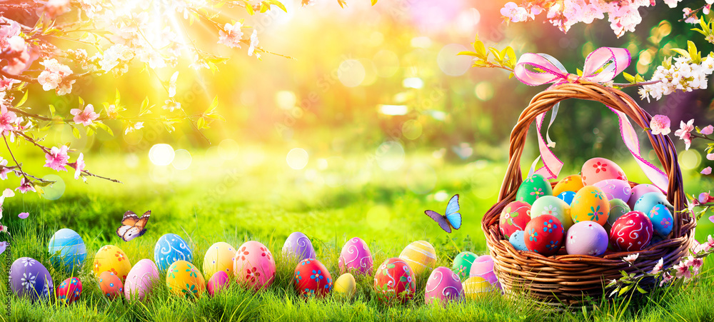 Fototapeta Easter - Painted Eggs In Basket On Grass In Sunny Orchard