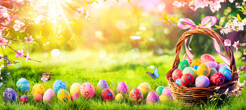 Photo Easter - Painted Eggs In Basket On Grass In Sunny Orchard