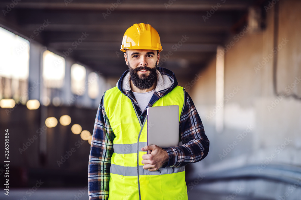 Fototapeta Portrait of highly motivated caucasian hardworking smiling bearded supervisor with helmet on head in vest and with laptop in hands posing on construction site.