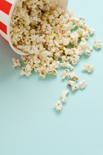 Vertical Image.Fresh Popcorn Spilled From The Paper Bowl On The Blue Surface.Empty Space For Text