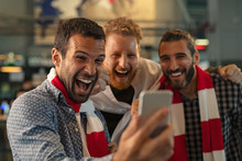 Excited Supporters Watching Football Match On Phone