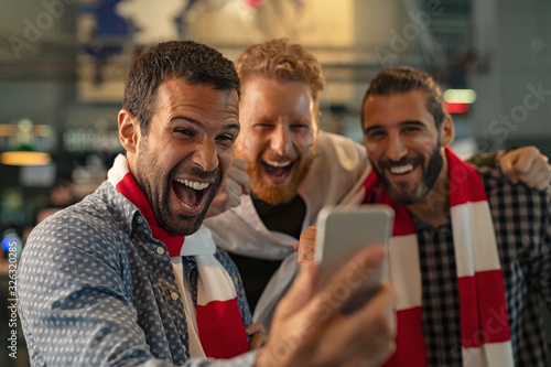 Vászonkép Excited supporters watching football match on phone