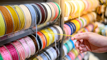 Male Hand Choosing Yellow Ric Rac Ribbon From Colorful Ribbon Rack In Craft Shop. Artisan And Handcraft Concept