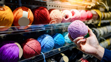 Male Hand Choosing Purple Yarn Ball In Knitting Shop Or Needlework Shop. Selection Of Colorful Yarn Wool On Shopfront. Shopping Lifestyle Concept