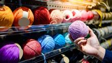 Male Hand Choosing Purple Yarn...