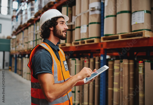 Fototapeta Young warehouse worker in hardhat and safety jacket using digital tablet while taking order and confirming stock availability using digital tablet obraz