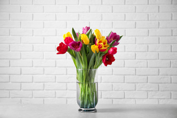 Beautiful spring tulips in vase on table near white brick wall