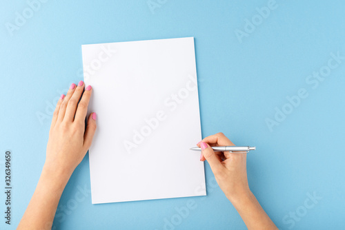 Fotomural Overhead shot of female hands writing with pen over empty white sheet of paper o
