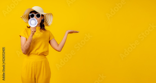 Cute and funny woman in yellow casual cloth style and wearing hat holding white megaphone for announcement and show hand to present product Canvas Print