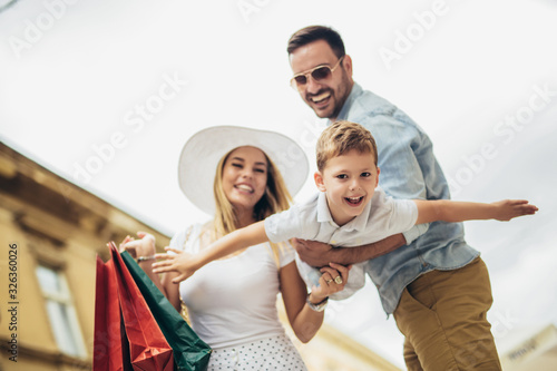 Happy family with shopping bags in the city. Fototapete