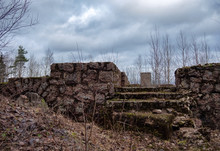The Ruins Of An Old House On The Banks Of A Wide River On A Cloudy Spring Day.