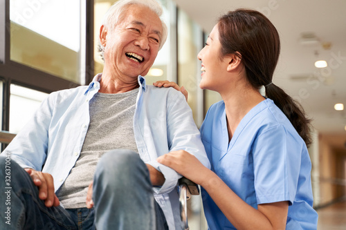 Leinwand Poster young friendly asian female caregiver talking to elderly man in nursing home