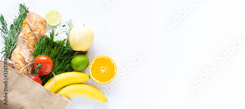 Photo Fresh organic vegetables, fruit, herbs and cheese in reusable paper bag on white marble background