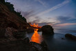 canvas print picture - Sunset on the beach among the rocks near the city of Denia. District of Valencia, Spain.