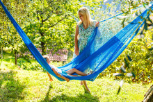 Close Up Portrait Of A Beautiful Young Mother And Her Five Years Old Daughter Laying Down In A Hammock Playfully During A Sunny Summer Day. Family Lifestyle Outdoors.