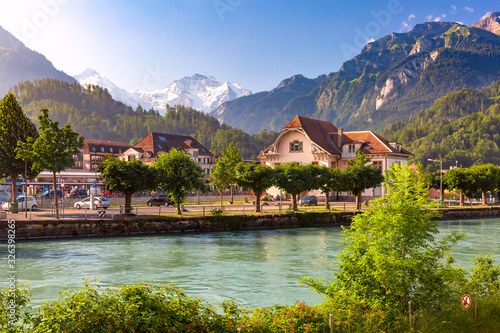 Train station and Aare river in Interlaken, important tourist center in Bernese Highlands, Switzerland. The Jungfrau is visible in background
