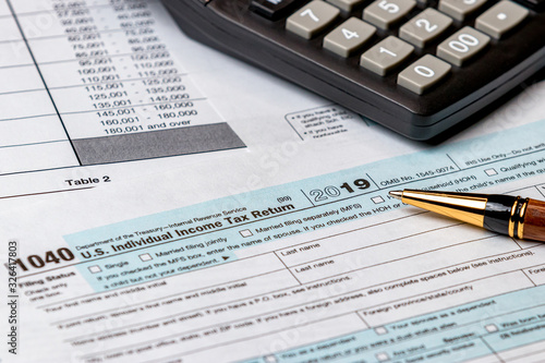 Fotomural 1040 income tax return form 2019 with calculator and pen