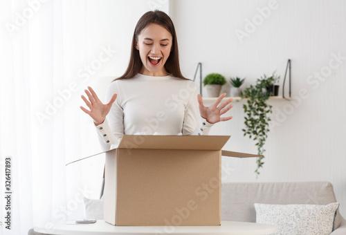 Obraz Positive client satisfied when open cardboard box parcel - fototapety do salonu